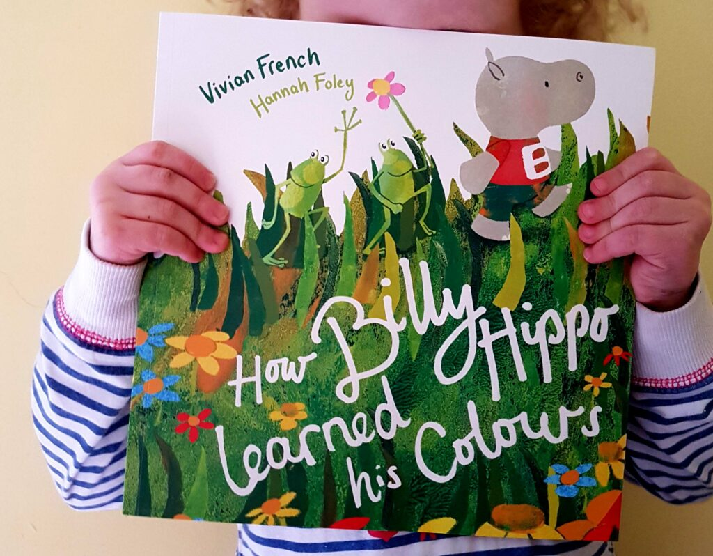 Little Girl holding How Billy Hippo Learned His Colours by Vivian French and Hannah Foley. Published by Little Door Books on Thursday 5th March 2020. All rights asserted for this image by Hannah Foley (www.hannah-foley.co.uk)